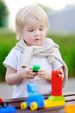 Litet barnpojke som spelar med färgrika plast- kvarter Fotografering för Bildbyråer