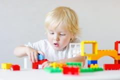 Litet barnpojke som spelar med färgrika plast- kvarter Arkivfoto