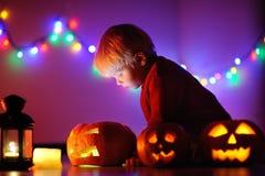 Litet barnpojke som spelar med halloween pumpor inomhus Arkivfoton