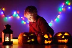 Litet barnpojke som spelar med halloween pumpor inomhus Royaltyfria Foton