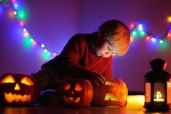 Litet barnpojke som spelar med halloween pumpor inomhus Royaltyfri Foto