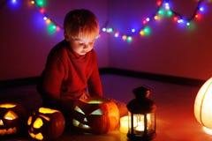 Litet barnpojke som spelar med halloween pumpor inomhus Royaltyfria Bilder