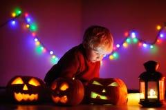 Litet barnpojke som spelar med halloween pumpor inomhus Royaltyfri Bild