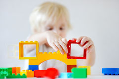 Litet barnpojke som spelar med plast- kvarter, fokus på händer Royaltyfri Foto