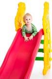Litet barnpojke som spelar på glidbanan Royaltyfria Foton