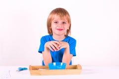 Litet barnpojkeanseende med ett magasin av Montessori material för en kurs på en vit bakgrund Övningsklipp med sax fotografering för bildbyråer
