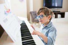 Litet barnpojken koncentreras på piano och musikaliska anmärkningar royaltyfri foto