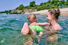 Litet barnpojken lär att simma med modern royaltyfria bilder