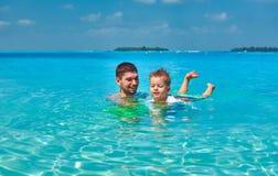 Litet barnpojken l?r att simma med fadern royaltyfri fotografi