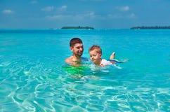 Litet barnpojken l?r att simma med fadern royaltyfria foton