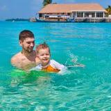 Litet barnpojken l?r att simma med fadern royaltyfri bild
