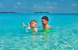 Litet barnpojken l?r att simma med fadern royaltyfri foto