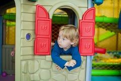 Litet barnpojken ser ut ur huset royaltyfria bilder