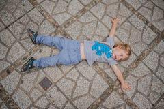 Litet barnpojken som tröttas i templet, ligger på trottoaren i chamen Tovers för Po Nagar Asien loppbegrepp royaltyfri foto