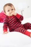 Litet barnsammanträde på bärande pyjamas för säng Fotografering för Bildbyråer