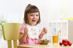 Litet barnsammanträde på tabellmat som är klar att äta i barnkammaren arkivfoton