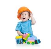 Litet barnungen i hardhat spelar med leksakkvarter över vit bakgrund royaltyfri fotografi
