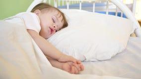 Litet behandla som ett barn att sova i sjukhussal på vit sängkläder Behandling av barn i sjukhusinställning Den sjuka ungen förbä stock video