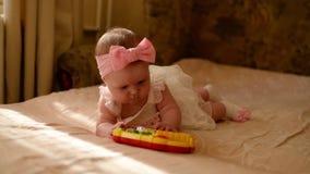 Litet behandla som ett barn att spela med leksaken hemma Lycklig barnflicka som lägger på säng i barnkammare stock video