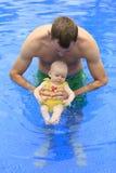 Litet behandla som ett barn flickan simmar i pölen med pappa Fotografering för Bildbyråer