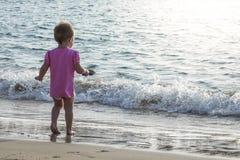 Litet behandla som ett barn flickan som spelar i vattnet, kantar på stranden royaltyfria foton