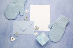 Litet behandla som ett barn handskar, tomt kort och packa in på blå tygbakgrund Lekmanna- lägenhet Top beskådar Royaltyfri Foto