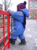 Litet behandla som ett barn pojken som bara går på gatan i höstklättringar på staketet royaltyfria bilder