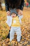Litet behandla som ett barn pojken lär att ta första steg som rymmer mammans händer i höst arkivbild