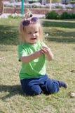 Litet behandla som ett barn pojken med den lyckliga framsidan på grönt gräs Arkivbild