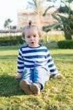 Litet behandla som ett barn pojken med den lyckliga framsidan på grönt gräs barfota Royaltyfria Foton