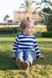 Litet behandla som ett barn pojken med den lyckliga framsidan på grönt gräs barfota Arkivfoto