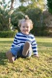 Litet behandla som ett barn pojken med den lyckliga framsidan på grönt gräs barfota Royaltyfri Bild