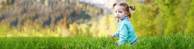 Litet behandla som ett barn sammanträde på gräset Sommar Baner för website _ Royaltyfria Foton