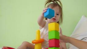 Litet behandla som ett barn spelar mjuka kuber och pyramiden i sjukhussal Barnlek med mång--färgad leksaker Utveckling av ungen stock video