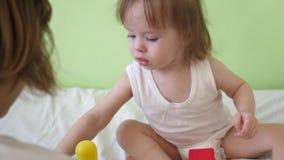 Litet behandla som ett barn spelar mjuka kuber och pyramiden i sjukhussal Barnlek med mång--färgad leksaker Utveckling av ungen arkivfilmer