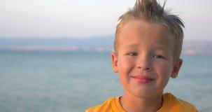 Litet blont barn på havsbakgrund lager videofilmer