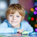 Litet blont barn som hemma spelar med bilar och leksaker Royaltyfria Bilder