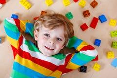 Litet blont barn som spelar med massor av färgrika plast- kvarter Arkivfoto