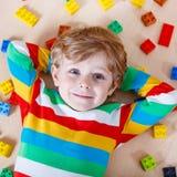 Litet blont barn som spelar med massor av färgrika plast- kvarter Royaltyfri Bild