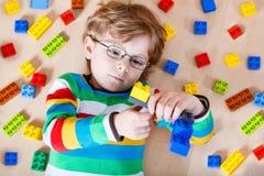 Litet blont barn som spelar med massor av färgrikt Arkivbilder