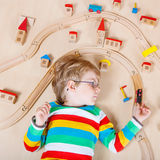 Litet blont barn som spelar med träjärnvägdrev inomhus Royaltyfri Bild
