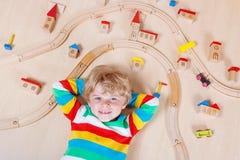 Litet blont barn som spelar med träjärnvägdrev inomhus Arkivfoto