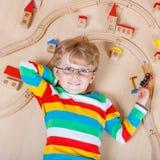 Litet blont barn som spelar med träjärnvägdrev inomhus Royaltyfria Foton