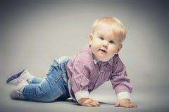 Litet blont behandla som ett barn pojkekrypning på jordningen Arkivfoton