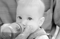 litet blont pojkedrinkvatten från en flaska royaltyfri bild