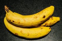 Litet brynte bananer på texturerad svart bakgrund Arkivbild