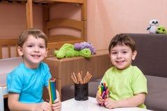 Litet caucasian barn som spelar med massor av inomhus färgrika plast- kvarter Lura den bärande skjortan för pojken och att ha rol Fotografering för Bildbyråer