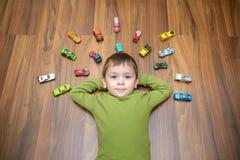 Litet caucasian barn som spelar med massor av leksakbilar inomhus Ungepojke som bär den gröna skjortan Lyckligt förskole- ha roli arkivfoto
