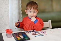 Litet charma behandla som ett barn pojken i en röda färgad målarfärgsittin för ämbetsdräkt attraktioner arkivfoto