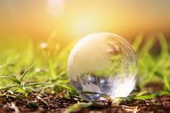 litet crystal jordklot för låg vinkel i gräset lopp och globalt frågebegrepp Royaltyfria Bilder